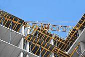 picture of construction crane  - Crane and building construction site against blue sky - JPG