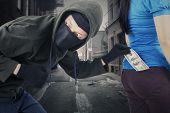 stock photo of stealing  - Portrait of male robber wearing mask and black jacket stealing money from pocket of his victim at the street - JPG
