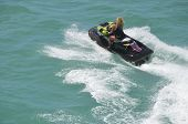 picture of ski boat  - Blond woman riding waves on a black jet ski in the florida intra - JPG