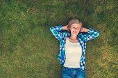 picture of beautiful senior woman  - Beautiful senior woman lying on a grass in a park - JPG