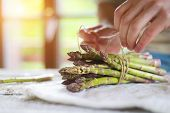 image of spears  - Bunch of fresh green asparagus spears tied with twine on a rustic wooden table - JPG