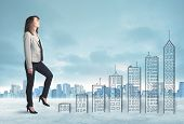 image of climb up  - Business woman climbing up on hand drawn buildings in city concept - JPG