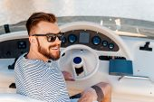 stock photo of steers  - Smiling young man holding hand on steering wheel while driving yacht - JPG