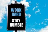 stock photo of humble  - WORK HARD STAY HUMBLE motivational quote written on road sign isolated over clear blue sky background with available copy space - JPG