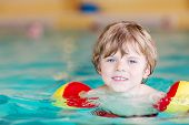 image of floaties  - Adorable little kid boy with swimmies learning to swim in an indoor pool - JPG