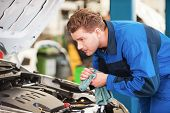 picture of concentration man  - Concentrated young man in uniform examining car and wiping his hands with rag while standing in workshop  - JPG