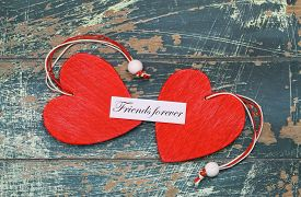 stock photo of  friends forever  - Friends forever card with two red wooden hearts on rustic wood - JPG