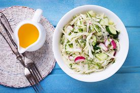 picture of grated radish  - Salad from cabbage herbs cucumber onion and radish in bowl on blue wooden background - JPG