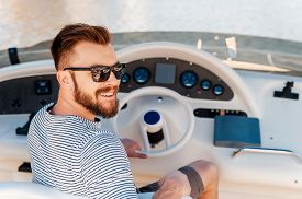 pic of steers  - Smiling young man holding hand on steering wheel while driving yacht - JPG