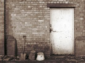picture of spade  - Old Victorian brick railway coal bunker with a spade and buckets in monochrome sepia - JPG