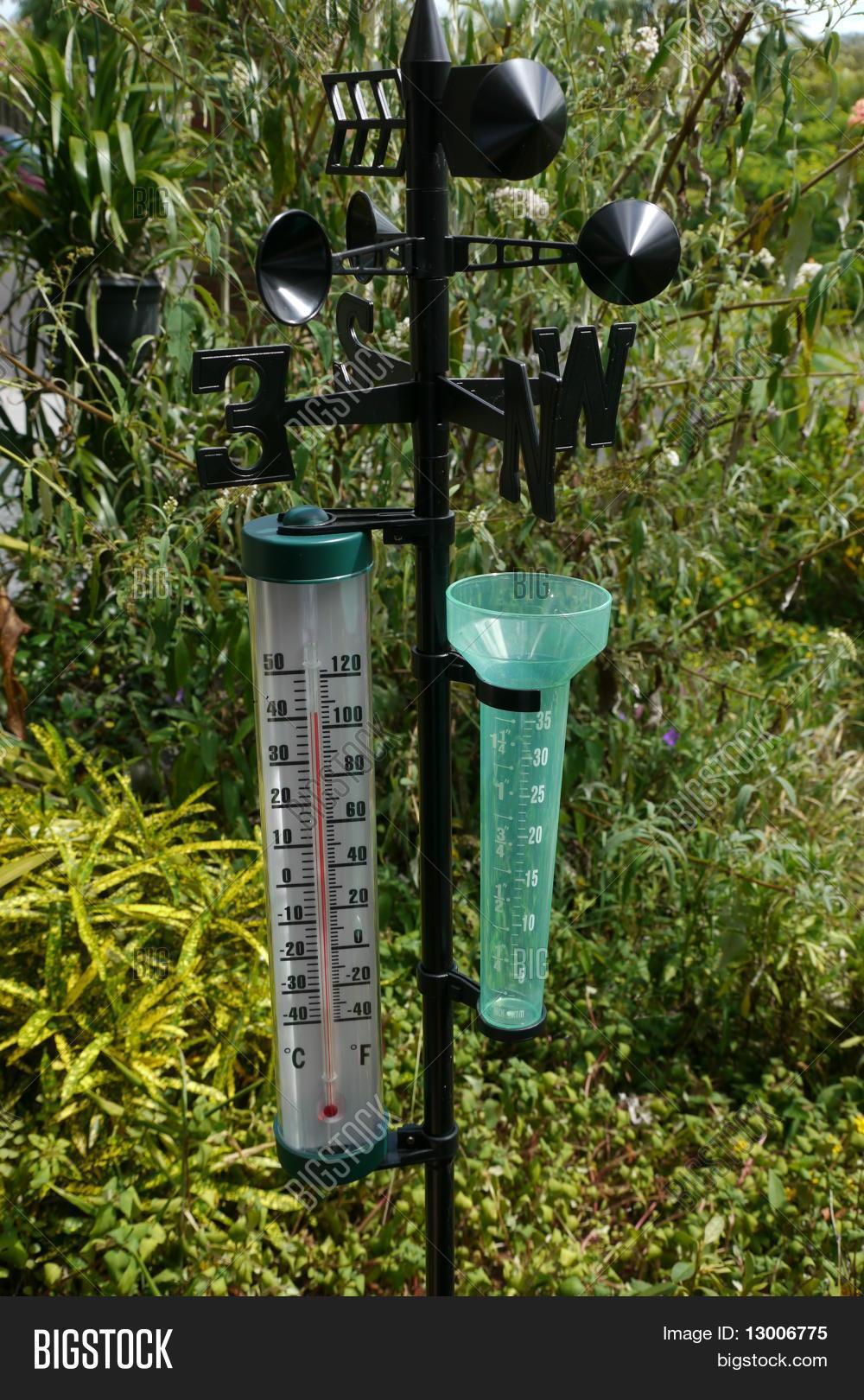 Garden thermometer rain gauge and weather vane Stock Photo
