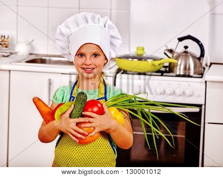 Child in cooking hat holding vegetable at kitchen. Child is on kitchen alone.