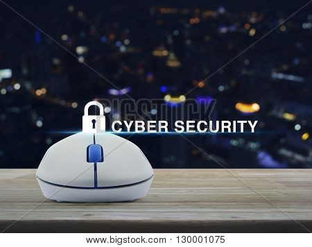Wireless computer mouse with key icon and cyber security text on wooden table in front of blurred light city tower
