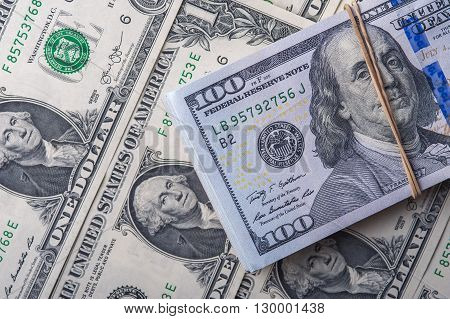 Stack of one hundred dollar bills on the background of one dollar bills