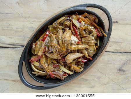 delicious spicy chicken pan on wooden table