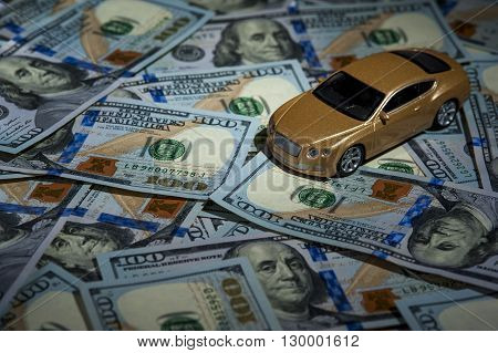 Toy automobile on the background of one hundred dollar bills