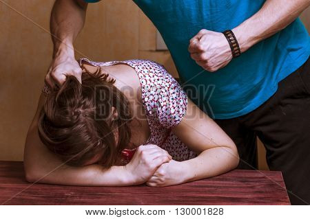 Domestic violence: aggressive man beating up his wife.