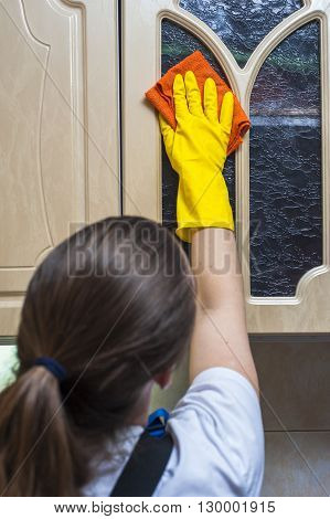 Woman scrubbing kitchen cupboard with rag. Selective focus.