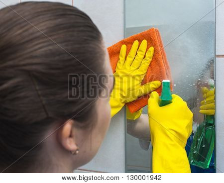 Woman with rag and spray cleaning the mirror. Housework and cleaning concept.