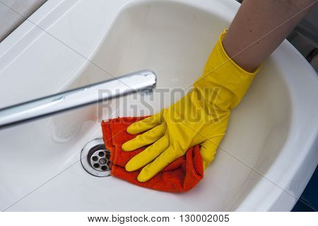 Woman's hand in yellow glove washing a sink. Cleaning concept.