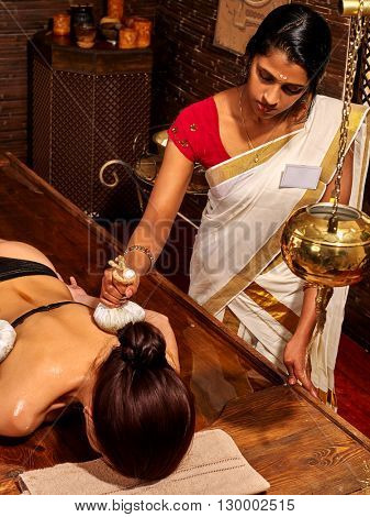 Woman having ayurvedic massage with pouch of rice. Exotic India massage.