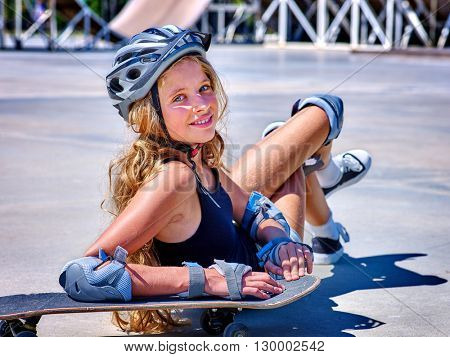 Teen girl in helmet sitting on his skateboard outdoor. Skateboard is extreme sport.
