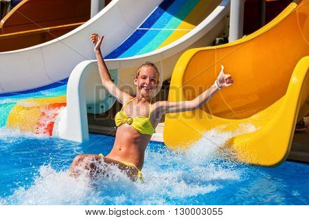 Child on water slide at aquapark and hand up. There are two water slides with flowing water in aqua park. Summer holiday. Child activities lifestyle Outdoor.