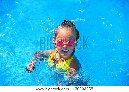 Portrait of child girl on water  in swimming pool . Children's healthy lifestyle into blue water. Summer holiday. Outdoor.