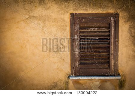 Closed wood window on an ancient yellow house wall