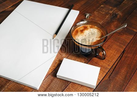 Blank paperwork template. Blank stationery set. Responsive design mockup on vintage wooden background. Paper letterhead coffee cup and pencil on wooden table background. Mockup for design presentations and portfolios. Top view.