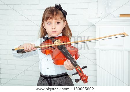 little girl playing the violin looking at camera