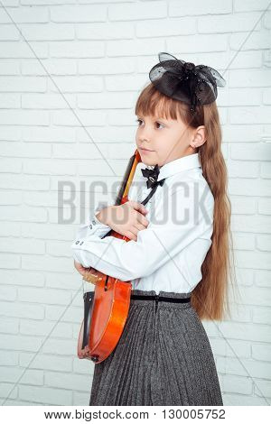 little girl hugging a violin and looking away