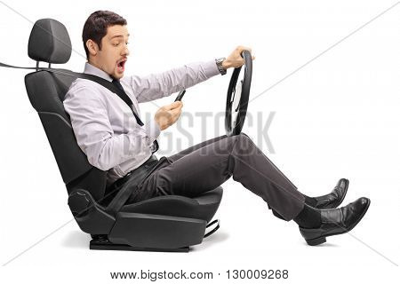 Young man driving and reading something on his phone isolated on white background