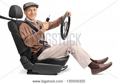 Cheerful senior man holding a steering wheel and a car key seated on a vehicle seat isolated on white background