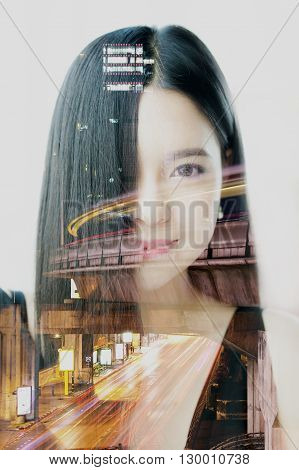 Double exposure of Asian woman dissolved with night cityscape.