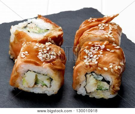 Delicious Smoked Eel Sushi with Sesame Seeds on Stone Plate closeup on White Plank background