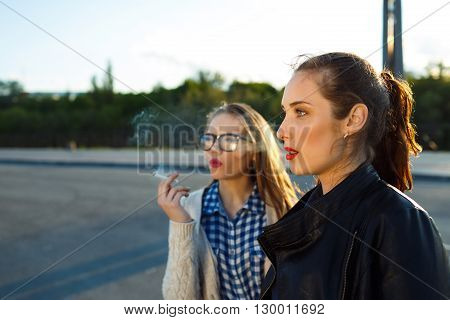 Two beautiful young girls to smoke while waiting - concept of bad habits