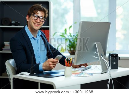 Handsome young man working from home office and using smartphone - modern business concept