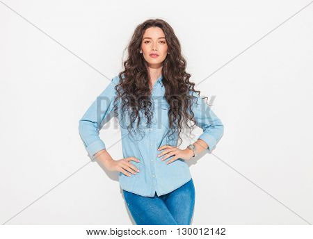 confident casual woman with hands on hips, leaning on studio wall