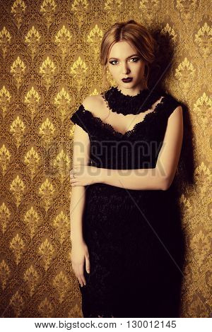 Evening look. Elegant young woman in black evening dress with dark make-up standing by a vintage wall.