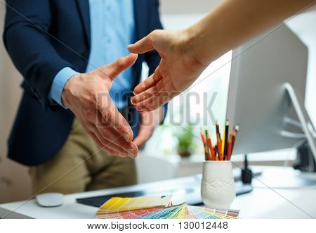 Young businessman and businesswoman shaking hands in office