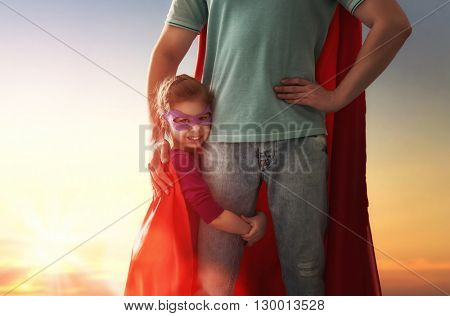 Happy loving family. Father and his daughter child girl playing outdoors. Daddy and his child girl in an Superhero's costumes. Concept of Father's day.