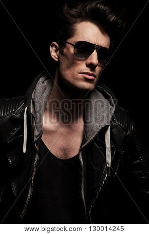 side view portrait of a cool young man in leather jacket and sunglasses looking away from the camera in studio