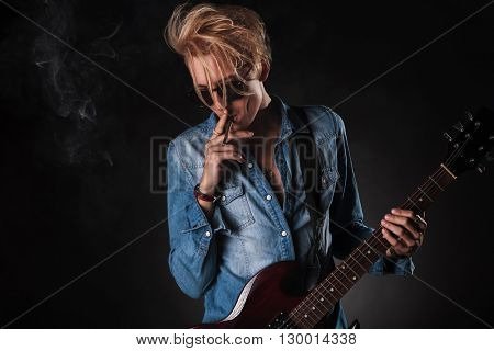 awesome young guitarist smoking and playing electric guitar in studio