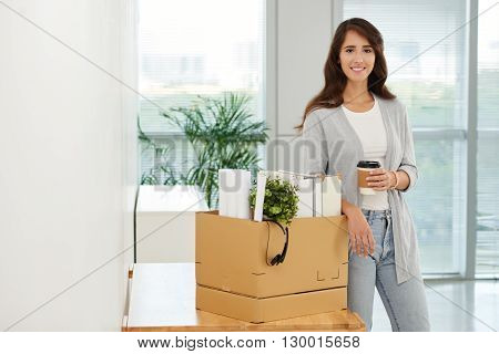 Business woman with box of her stuff standing in new office