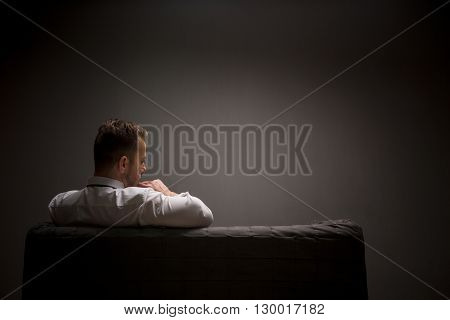 Sad businessman sitting on comfortable sofa after hard-working day and continues thinking about work. Studio shot. Back view.