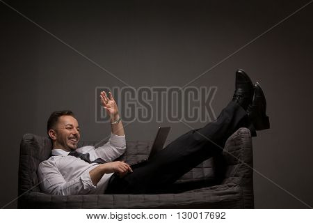 Happy businessman lying on comfortable sofa with laptop computer. Smiling man waving to photographer in studio. Studio shot.