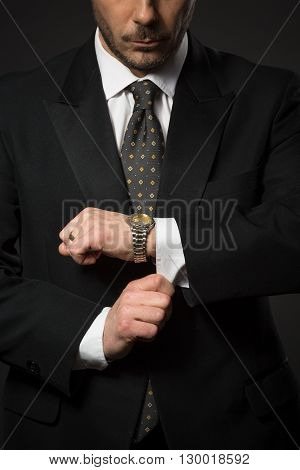 Closeup of businessman in black suit correcting sleeve in studio. Man preparing for work or business meeting.