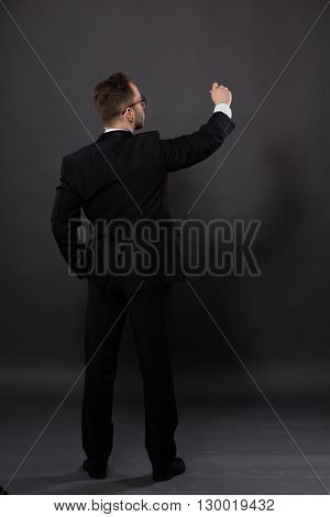 Back view picture of businessman in full length in studio. Man in black suit keeping one hand in pocket and writing something on wall.