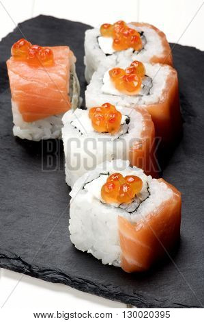 Delicious Sushi with Smoked Sliced Salmon and Gourmet Red Caviar on Stone Plate closeup on White Plank background